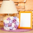Colorful photo frame, lamp and flowers on wooden table on stone wall background — Stock Photo #22482959