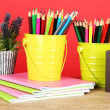 Colorful pencils in two pails with copybooks on table on red background — Stok fotoğraf