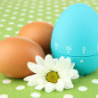 Blue egg timer and eggs, on color background — Zdjęcie stockowe