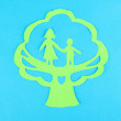 Green cut out paper tree with people inside, on color background - Stock Photo