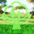Green cut out paper tree with inside, on green grass on bright background — Stock Photo