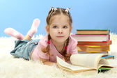 Cute little girl with colorful books, on blue background — Zdjęcie stockowe