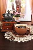 Tazza di caffè con sciarpa e laminatoio di caffè sul tavolo in sala — Foto Stock