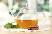 Teapot with mint and cinnamon on table in room — Stock Photo