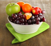 Bowl with fruits, on wooden table — Foto Stock