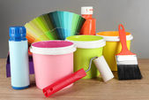 Paint pots, paintbrushes and coloured swatches on wooden table on grey background — Stock Photo