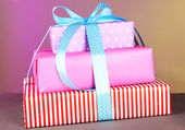 Gift box tied with a ribbon on a color background — Stock Photo