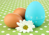 Blue egg timer and eggs, on color background — Stock Photo
