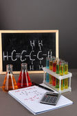 Test tubes with colorful liquids and formulas on grey background — Stock Photo