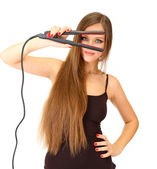 Woman doing hairstyle with hair straightener, isolated on white — Stock Photo