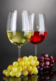 Red and white wine in glasses on grey background — Stock Photo