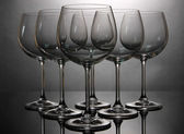 Empty wine glasses arranged on grey background — Stock Photo