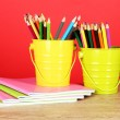 Colorful pencils in two pails with copybooks on table on red background — Photo
