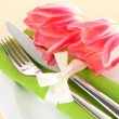 Festive dining table setting with tulips on beige background - Stockfoto