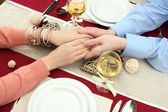 Hands of romantic couple over a restaurant table — Stock Photo