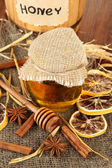 Jar of honey, wooden barrel, drizzler and dried lemons on wooden background — Stock Photo