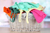 Clothes in wooden basket on table in room — Stock Photo