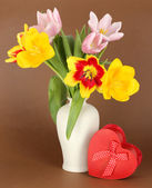Beautiful tulips in bucket with gift on brown background — Stock Photo
