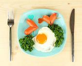Salchichas en forma de corazones, huevos revueltos y perejil, en placa de color, sobre fondo de madera — Foto de Stock