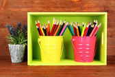 Colorful pencils in pails on shelf on wooden background — Stock Photo