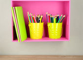 Colorful pencils in pails on shelf on beige background — Foto Stock