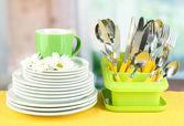 Placas, garfos, facas, colheres e outros utensílios de cozinha em guardanapo de cor, no fundo brilhante — Foto Stock
