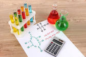Test tubes with colorful liquids and formulas on table — Stock Photo