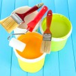 Set for painting: paint pots, brushes, paint-roller on blue wooden table — Stock Photo #22532173
