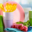 Multicolored plastic tableware on table with tulips close up — Stock Photo