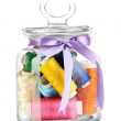Stock Photo: Glass jar containing various colored thread isolated on white