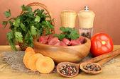 Surowy wołowiny z ziół i przypraw na drewnianym stole na brązowym tle — Zdjęcie stockowe