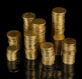 Many coins in columns isolated on black — Stock Photo