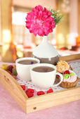 Cups of tea with flower and cakes on wooden tray on table in cafe — Stock Photo