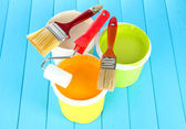 Set for painting: paint pots, brushes, paint-roller on blue wooden table — Stock Photo