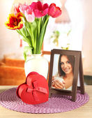 Beautiful tulips in bucket with gifts on table in room — Stock Photo