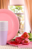 Multicolored plastic tableware on window background — Stock Photo