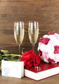 Trauringe auf bibel mit rosen und gläsern champagner auf hölzernen hintergrund — Stockfoto