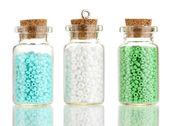 Małe butelki pełne kolorowych paciorków na białym tle — Zdjęcie stockowe