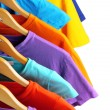 Stockfoto: Lots of T-shirts on hangers isolated on white