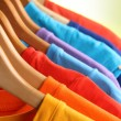 Stock Photo: Lots of T-shirts on hangers on green background