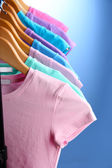 Lots of T-shirts on hangers on blue background — Stock Photo