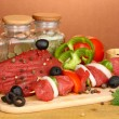 Raw beef meat marinated with herbs and spices on wooden table on brown background — Stock Photo