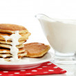 Sweet pancakes on plate with condensed milk isolated on white — Stock Photo