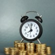Alarm clock with coins on grey background — Stock Photo