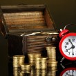 Alarm clock with coins in chest on dark background — Stock Photo