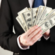Business man holds lot of money on grey background - Stock Photo
