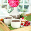 Cups of tea with flower and cake on wooden tray on table in room — Stock Photo #22635101