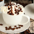 Cup of whipped cream coffee on wooden table close up - Stock Photo