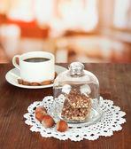 Dulces de chocolate bajo cubierta de cristal y bebida caliente sobre fondo brillante — Foto de Stock