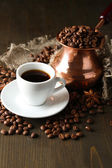 Cup of coffee and pot on wooden background — Stock Photo